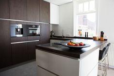 Deze moderne keuken heeft een kastenwand van donkerbruin hout. Dit zorgt voor een warme en natuurlijke uitstraling. Daarnaast heeft de keuken een kookeiland met een bar. Zo wordt de keuken meer betrokken bij de woonkamer. Het eiland is in een witte kleur met een zwart aanrechtblad. De kastjes zijn voorzien van greeploze lades waardoor het er strak en modern uitziet. Kitchen Island, Home Decor, Island Kitchen, Decoration Home, Room Decor, Home Interior Design, Home Decoration, Interior Design