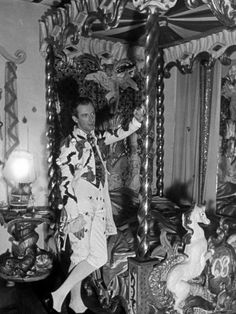 Cecil Beaton in the Circus room, posing in an 18th-century-style jacket, with surreal touches, for a fete champetre, hosted at his country house, Ashcombe.