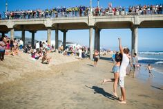 Adorable beach proposal. Look at the people on the pier to see what their shirts spell out. I love the photography.