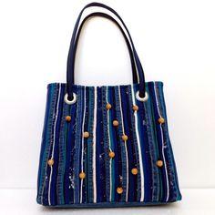 Kekseliäästi somistettu, jämäkän oloinen farkkulaukku. -beautifully decorated denim bag