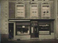 """café de """"l'hotel de ville"""" et de la boucherie Dèstrée. A droite Ferdinand Dèstrée et à gauche son épouse Justine Parent. La photo date de 1926 (place du marché)"""
