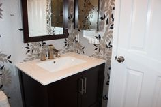 Modern bath features free standing vanity with matching mirror, textured tile floor and bold, beautiful wallpaper. #ranchointeriordesign