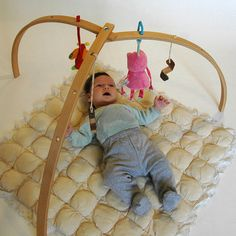 Got this instead of the plastic gym / mat combo. Super excited! Wooden baby gym for hanging baby mobiles on Etsy.
