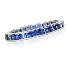 Incomparable Tiffany Sapphire Eternity Ring - Channel set with 30 square cut natural sapphires, mounted in platinum. Late 20th century. The Three Graces