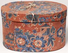 "Rhode Island chintz-covered oval bandbox. Sewn paperboard covered in printed cotton chintz in shades of blue and white on a red background with original cotton tape, turned wooden buttons to secure the lid, and lined with newspaper from Providence, Rhode Island. Dated 1834. W: 12½"" x H: 7½"" x D: 9¾"""
