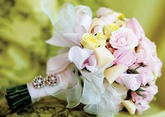Bridal bouquet of yellow and pink spray roses and yellow and pink fabric roses adorned with antique earrings by Cheryl Duncan of Village Flowers and Mercantile.