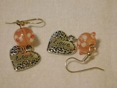 2 inches long  3/4 inch silver colored heart, dangling from a pink spotted glass lampwork bead embellished with lampwork flowers.