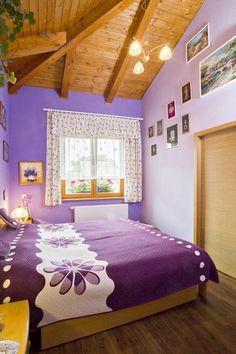 """Výmalba v barvách levandule dodala ložnici příjemnou """"pastelovou"""" atmosféru a zvýraznila dřevěný strop."""
