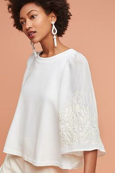 Poncho pullover in white with embroidered sleeves. Trendy outfit perfect for a special dinner.