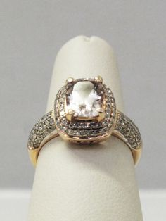 This gorgeous morganite ring sports a halo encrusted with diamonds, all set in rose gold.