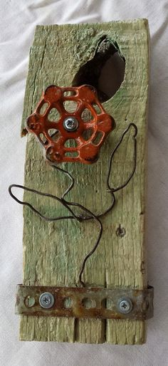 Flower. Faucet handle, old rusty wire and metal strapping on weathered wood. Hanger on back. Small, 9 inches tall. Recycle upcycle repurpose scavenge assemblage