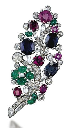 AN ART DECO MULTI-GEM AND DIAMOND BROOCH, BY CARTIER  The pavé-set diamond stem decorated with cabochon emeralds, cushion-shaped sapphires and rubies, to the circular-cut diamond collet detail, 1930s, 6.2 cm, with French assay mark for platinum Signed Cartier Paris, no. L2013