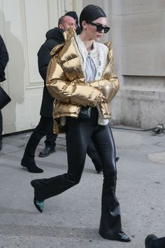 Kendall Jenner is always one of our street style stars!  The model was spotted in Paris wearing the off-duty model uniform: a gold puffer jacket, a pair of wide-legged pants, a white knit sweater and a gray tee.