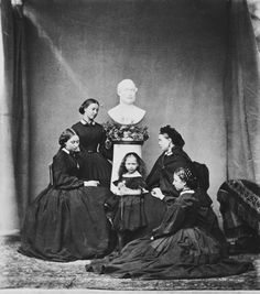 Mar 1862; Princess Alice, seated; Princess Helena, standing behind Alice; bust of Prince Consort; Princess Beatrice standing; Princess Royal seated, head profile left; Princess Louise, seated on floor holding Princess Royal's hand.