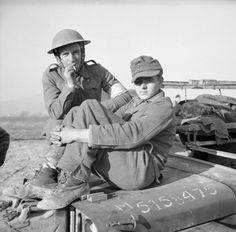 A British soldier with a young German prisoner sitting on the bonnet of a jeep, 21 January 1944.
