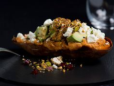 Roast Sweet Potato with Hummus and Dukkah with chunks of avocado and tofu on black background