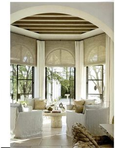 iron french doors, slipcovered furniture, simple roman blinds over arched doors - Greige