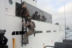 U.S. Navy SEALs assigned to a west coast-based SEAL Team debark a hostile vessel off the coast of San Diego, CA. Naval Special Warfare Boat Team (SBT) 12 assisted in the operation by providing small boat insertion and extraction to and from the boarded vessel. (U.S. Navy photo by Mass Communication Specialist 3rd Class Kristopher Kirsop)