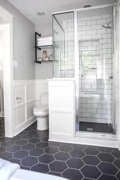 We used large, hexagonal flooring throughout the whole bathroom. I love the way it paired with the classic white subway tile we used in the shower. remodel A Master Bathroom Renovation Bathroom Grey, Bathroom Renos, Bathroom Flooring, Bathroom Vanities, Bathroom Cabinets, Bathroom Interior, Subway Tile Bathrooms, Dark Floor Bathroom, Design Bathroom