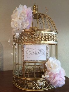 """This chic + pretty in pink gold birdcage is with prettified with lace, hand calligraphy that reads """"Cards"""", pink + white delicate blooms with touches of pearls. This birdcage is the perfect accessory for cards + gifts given at a bridal shower, baby shower or beautiful wedding. This pretty cage can be used as a decorative piece in its own + can be kept as a keepsake for years to come.   This item was used once at my wedding to hold the cards. I'm charging $65.00 for the cage and ..."""
