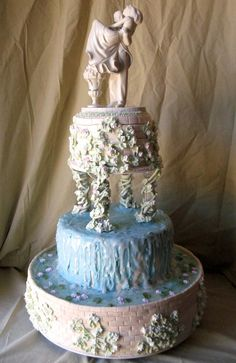 Artistic three tier  wedding fountain cake design, in blue and ivory. Decorated with a classic bridal and groom figurine wedding cake topper