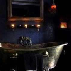 Sumptuous bathroom with silver metal claw foot tub, candlelight and dark blue walls