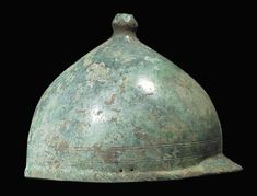 A ROMANO-CELTIC BRONZE HELMET OF MONTEFORTINO TYPE   CIRCA 3RD CENTURY B.C./1ST CENTURY A.D.   Peaked at the back, with finial above, the sides pierced for cheek-piece attachments, small restoration on one side edge  7½ in. (19 cm.) high