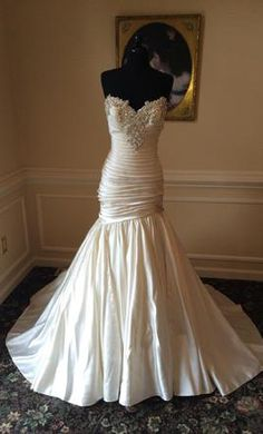 A lovely fitted bodice wedding dress with bling on the sweetheart neckline.  This ruched bodice wedding dress begins to flare from the lower hip. We can create a custom wedding dress like this for you for a reasonable price.  Contact us for details at https://www.dariuscordell.com/featured_item/custom-wedding-dresses-custom-bridal-gowns/