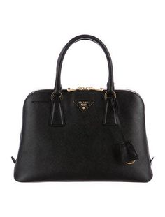Black Saffiano leather Prada Small Promenade bag with gold-tone hardware, single flat removable shoulder strap, dual rolled top handles, logo placard front, protective feet at base, three interior compartments; one with zip closure, tonal jacquard lining, four interior pockets; one with zip closures and two-way zip closure at top. Includes clochette and dust bag. Shop Prada handbags on sale at The RealReal.