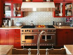 A mixture of colors and materials found in the vibrant #red cabinets, patterned tile backsplash and stainless-steel oven create a polished, energized #kitchen.