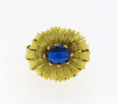 18K gold ring features a textured flower motif featuring a blue stone center. Ring size 7, top measures 21.5mm x 18.2mm. Marked with European gold punch marks. Tested 18K. Weight - 8.8 grams. Gemstones have not been graded for color and clarity ,and tested for  clarity and color enhancement, unless stated otherwise. Watches are guaranteed to be in running order, if described as such, at the time of listing only. Watches have not been tested for features functionality, unless otherwise…