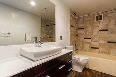 Recessed lights and a large scale frameless vanity mirror solves the problem for this windowless bathroom.