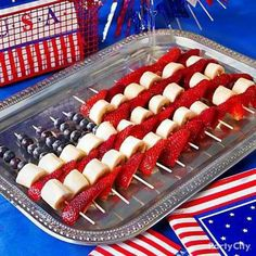 Create an American flag using bananas, strawberries and blueberries on kabob skewers