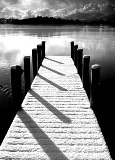 This picture shows value. It has light and dark colors and shows highlights and shadows. You can see shadows from the poles on the dock. There are highlights on the water from where the sun is shining on it.