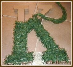 Hobby Lobby letter wrapped in Christmas tree garland, add a pretty ribbon and hang on front door. Such a great (and inexpensive) idea