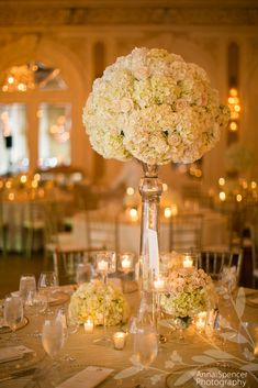 Anna and Spencer Photography, Atlanta Wedding Photographers. White & Light Green Hydrangeas With Pale Pink Roses Atop a Tall Glass Pedestal - Wedding Reception Table Floral Arrangement. Wedding Reception at the Club Room on Sea Island, Georgia.