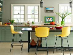 idée déco cuisine moderne avec îlot central en noir corbeau, tabourets jaunes et meubles en vert pâle