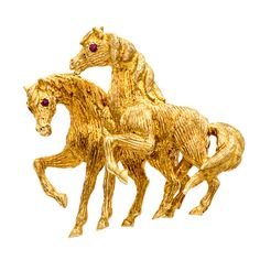 This beautiful brooch features a pair of horses rendered in textured 18-karat yellow gold. Round-cut ruby gemstone eyes characterize this lovely pin.