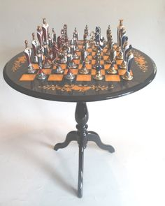 Mesa circular para jogo de xadrez, de madeira laqueada, tampo na tonalidade azul decorado com flores. Acompanha 32 peças de metal, sendo 16 nas cores azul, branca e dourada e 16 nas cores vermelha, branca e prateada.