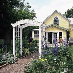 An arbor over the front walk would be lovely. Wisteria or climbing roses would be perfect.