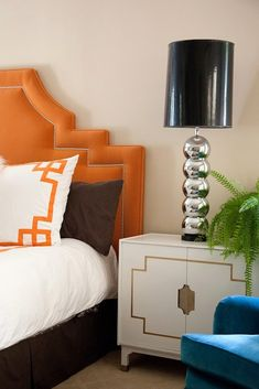 orange headboard with nailhead trim, blue velvet chair, vintage, white, lacquer, Hollywood Regency, nightstands cabinets, polished chrome stacked balls lamps with black vinyl lamp shades, brown pillows and white bedding with orange Greek key trim.
