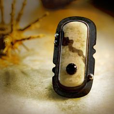 Black onyx sits atop a jasper cabochon, set in antiqued copper by Savage BonesAndStones. Love the notches in the bezel base.