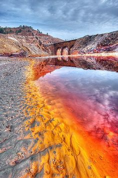 Rio Tinto, Huelva, Spain.  As a result of nearby mining, Río Tinto is notable for being very acidic (pH 2) and its deep reddish hue is due to iron dissolved in the water. Acid mine drainage also creates heavy metal concentrations in the river's waters.