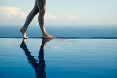 Woman walking along edge of infinity pool, low section, with ocean in background