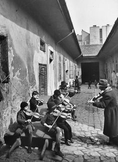 Gypsy children being taught to play the violin in a courtyard of one of the poorer houses of Budapest, Hungary, 1939