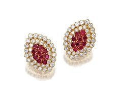 PAIR OF RUBY AND DIAMOND EARCLIPS, VAN CLEEF & ARPELS, NEW YORK.  The navette motifs set with clusters of 20 round rubies within borders of 72 round diamonds weighing approximately 9.25 carats, mounted in 18 karat gold, signed VCA, numbered N.Y. 44356.