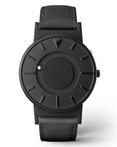 """The Eone Bradley Black Canvas Watch features a minimalist face with raised markers at each hour. To increase tactile legibility, there is a triangular marker indicating """"12"""", and elongated markers for """"3"""", """"6"""", and """"9"""". Time is indicated by two ball bearings."""