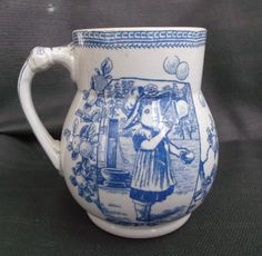 This is an old blue, white, transfer-ware cup showing a young girl blowing bubbles. She is standing in front of a well and is framed with fruit growing on the vine. Marked on the bottom Old Hall E'ware, England and then Mother Hubbard. This...