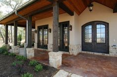 Ranch home with overhangs and posts light stucco and black windows and doors with wood ceiling lighting etc Curb appeal