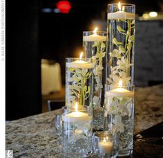 tall vases with flowers, glass stones and candles